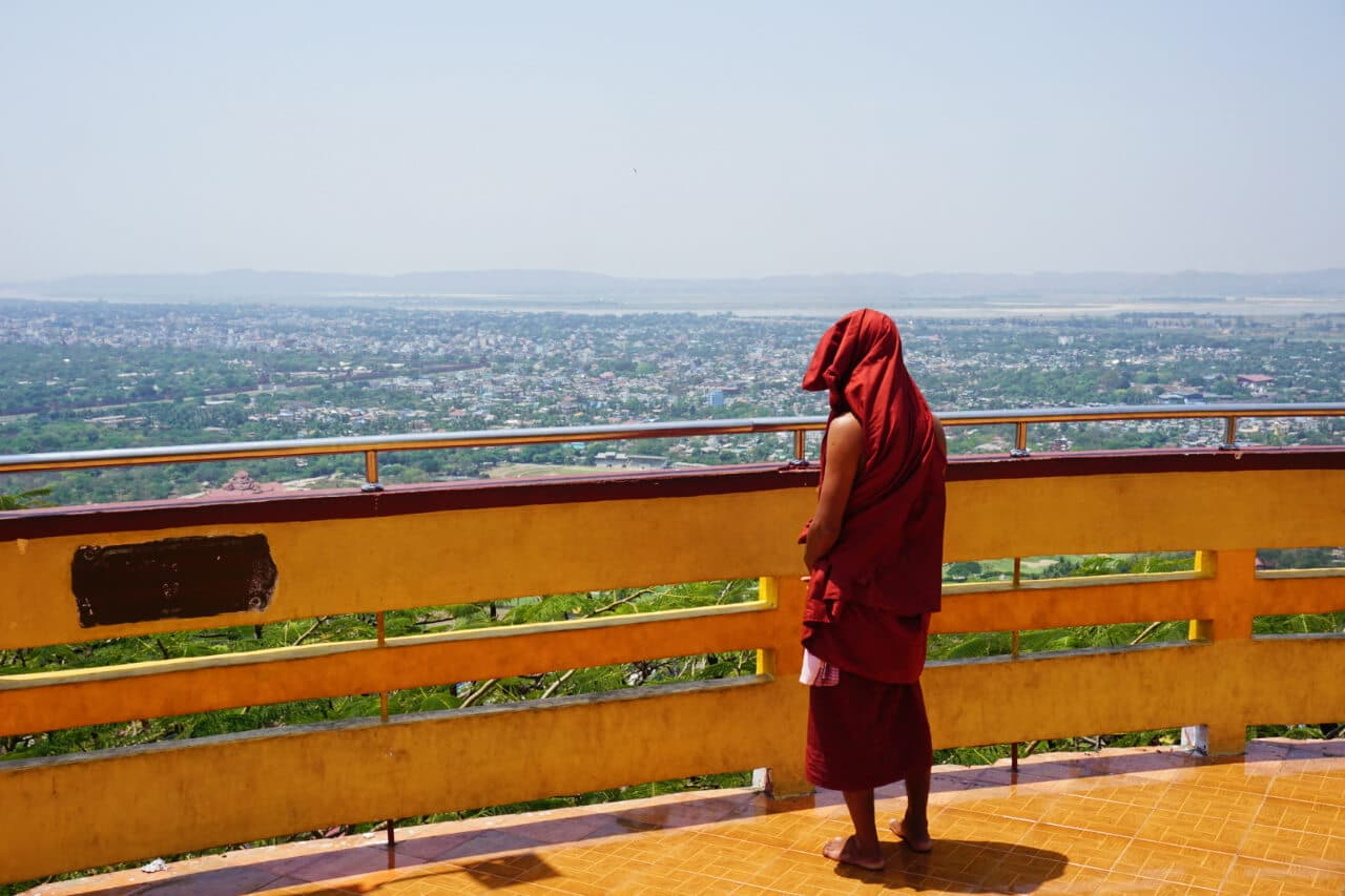 Myanmar photos monk looking over Mandalay cityscape