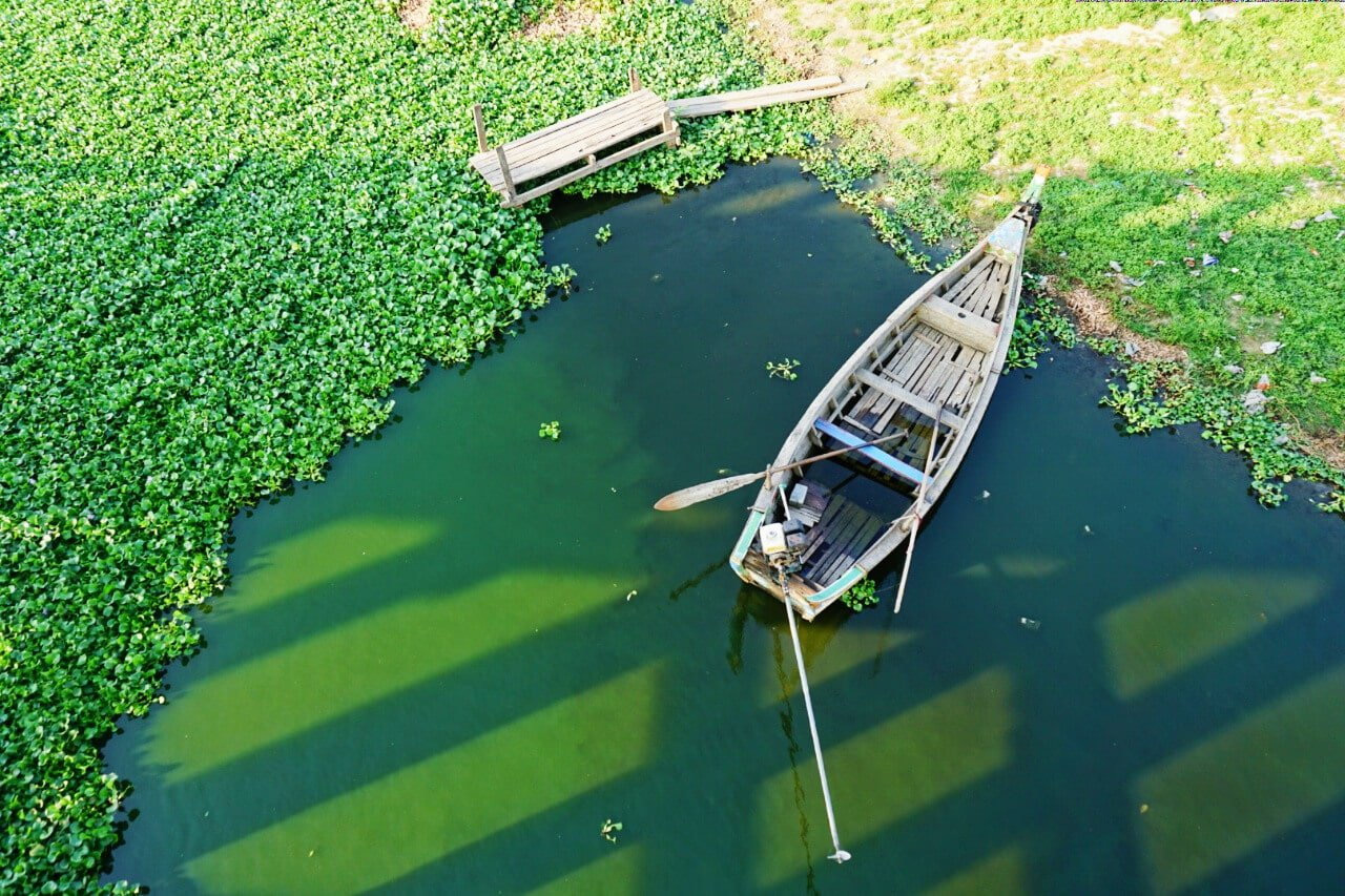 Myanmar photos boat on green water under U Bein bridge