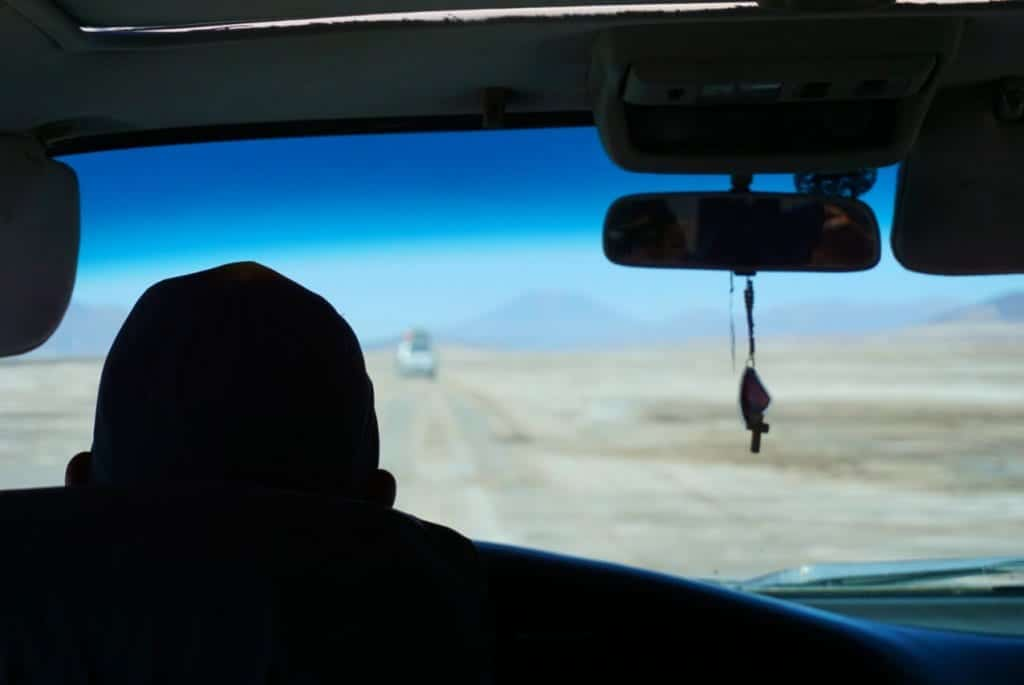 Car driving a tour on Uyuni's salt flats