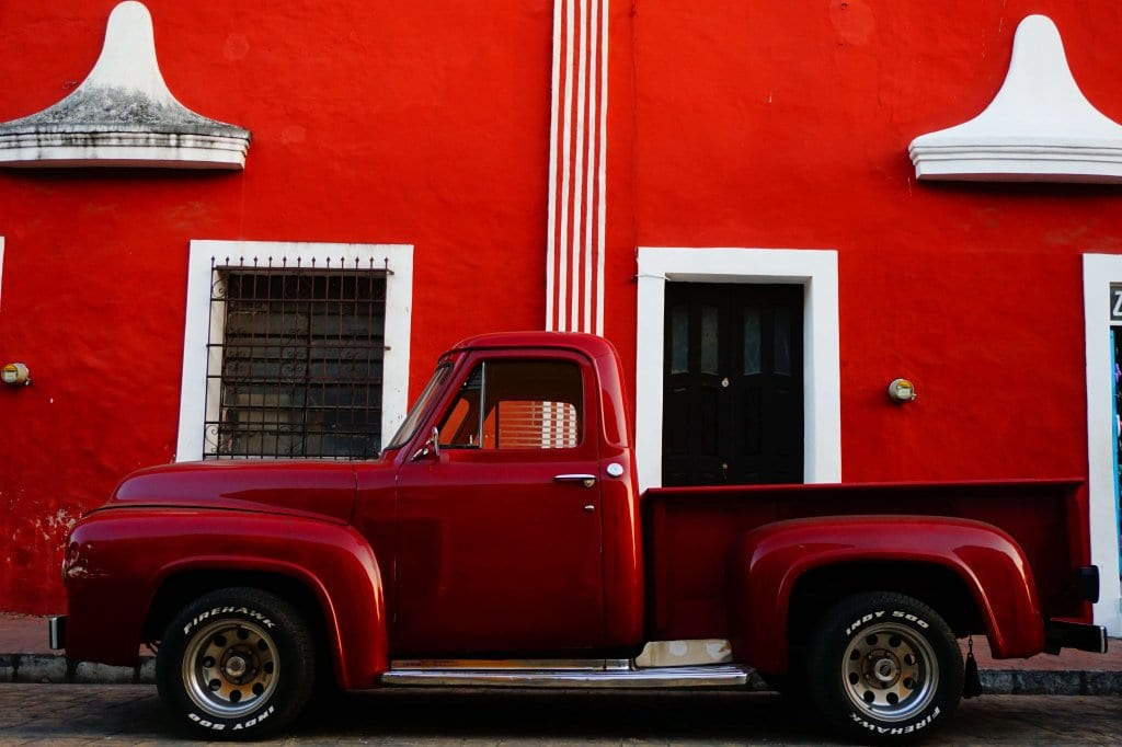 A red truck against a red wall in Valladolid Mexico