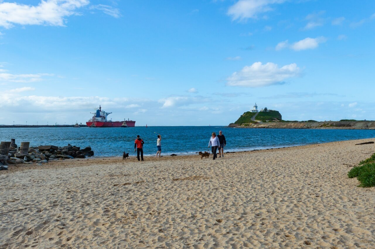 A large coal tanker ship sails out of Newcastle port, taken from Horseshoe Beach, with Newcastle Lighthouse in view