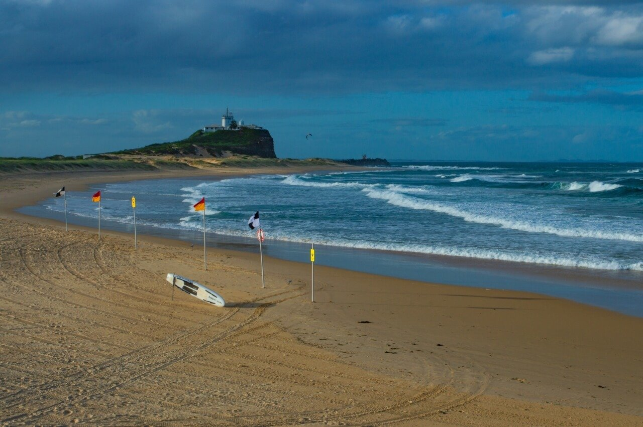 Nobbys beach, one of the top things to do in Newcastle Australia, with Newcastle Lighthouse in the distance