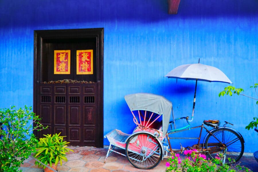 An old trishaw in front of the Blue Mansion