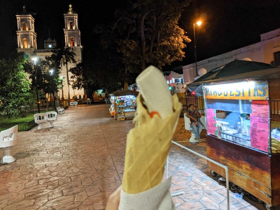 A marquesita near a vendor stand in the Valladolid city square