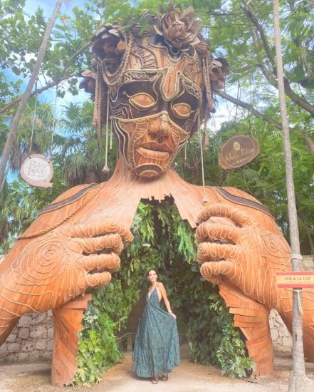 Woman standing in front of the statue at Ahau Tulum