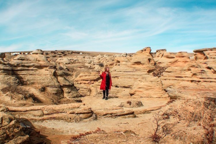 Taylor stands among red rock hoodoos in Writing-On-Stone Provincial Park in Alberta Canada