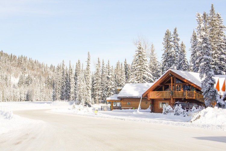 A wooden chalet stands among snowy trees and a road near Cochrane, Alberta Canada
