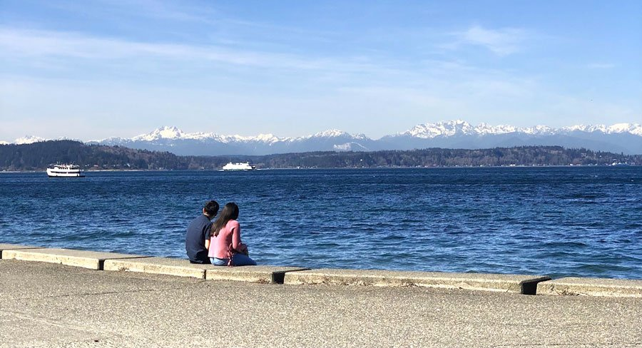 A man and a woman sitting by the Alki Beach