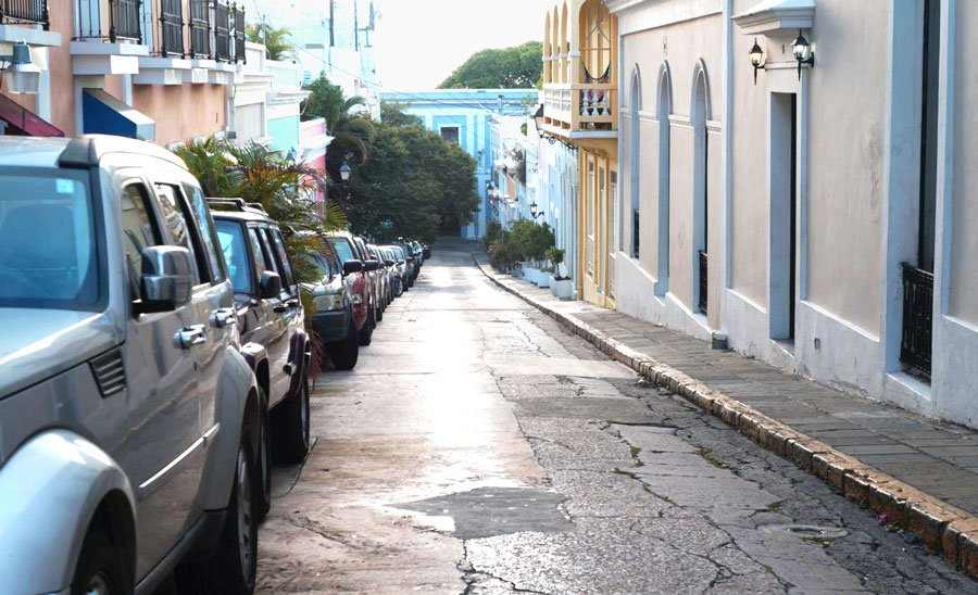 View of cars parked in an alley with colorful houses