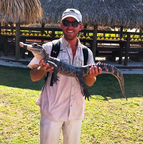 View of the author holding a small alligator