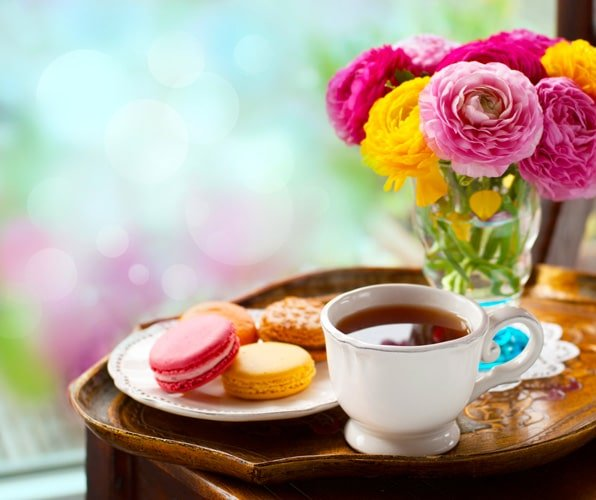View of coffee, macarons, and a colorful flower on a table