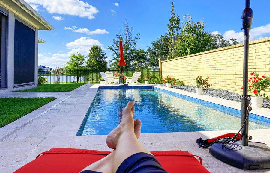 View of a backyard swimming pool with a clear blue sky