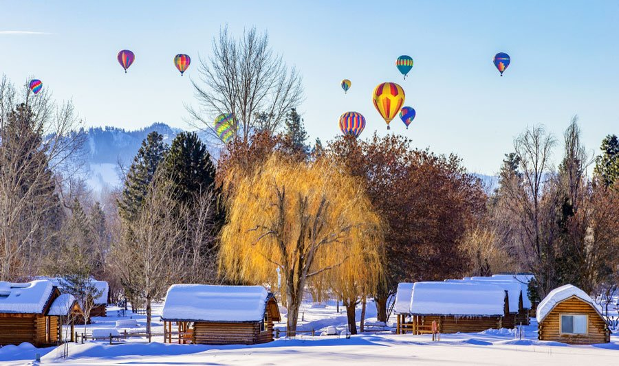 View of colorful hot air balloons above a snowy village