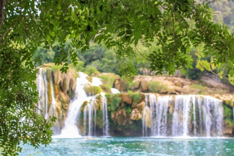 One of the main waterfalls in Krka National Park, surrounded by foliage
