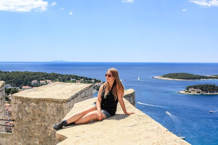 Taylor sits on the walls of the Spanjola Fortress in Hvar, Croatia, with the Adriatic Sea, islands, and sailboats in the background.