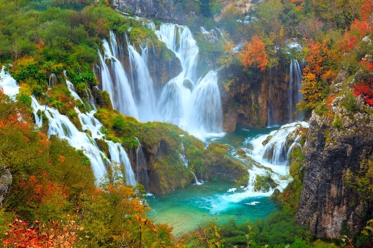 The waterfalls of Plitvice National Park in Croatia surrounded by fall foliage