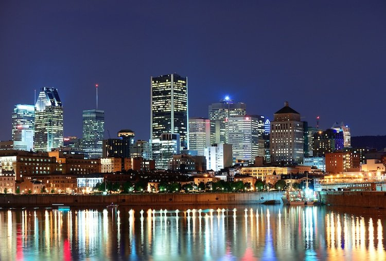 Montreal, Canada skyline at night with city lights shining against the river