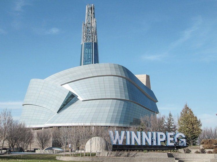 """The human rights museum in Winnipeg Manitoba, with a """"Winnipeg"""" sign in front."""