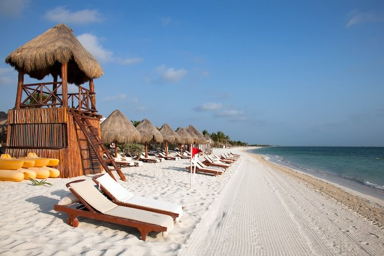 Playa Del Carmen beach in Mexico lined with a lifeguards hut and sun loungers
