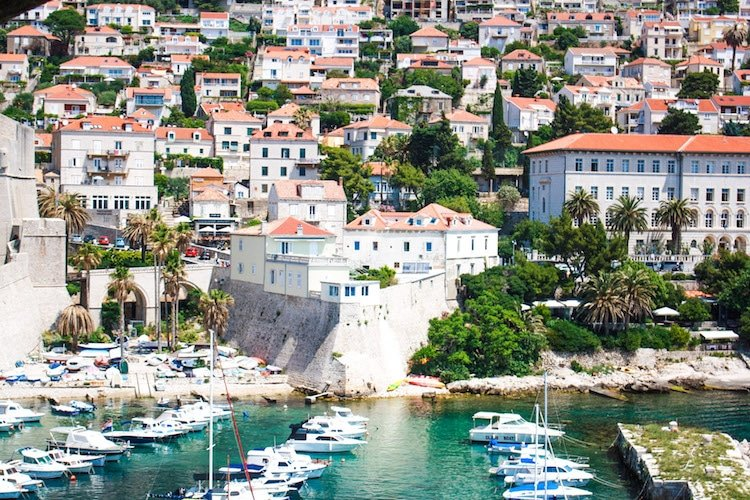 The Dubrovnik harbor in Croatia with sailboats, yachts, and houses in the background