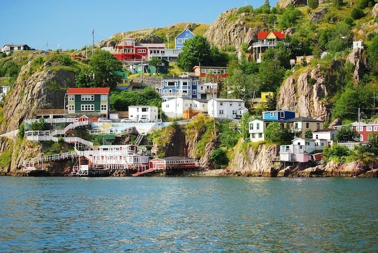 Houses dot a cliffside in front of the sea in Newfoundland, Canada