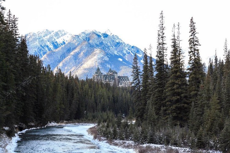 The Fairmont Banff castle sits behind a river and trees with mountains in the background.