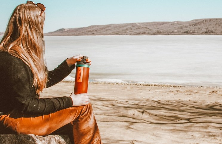 Taylor sits on a rock while holding a Grayl Geopress water filter. A lake, hills, and beach are in the background.