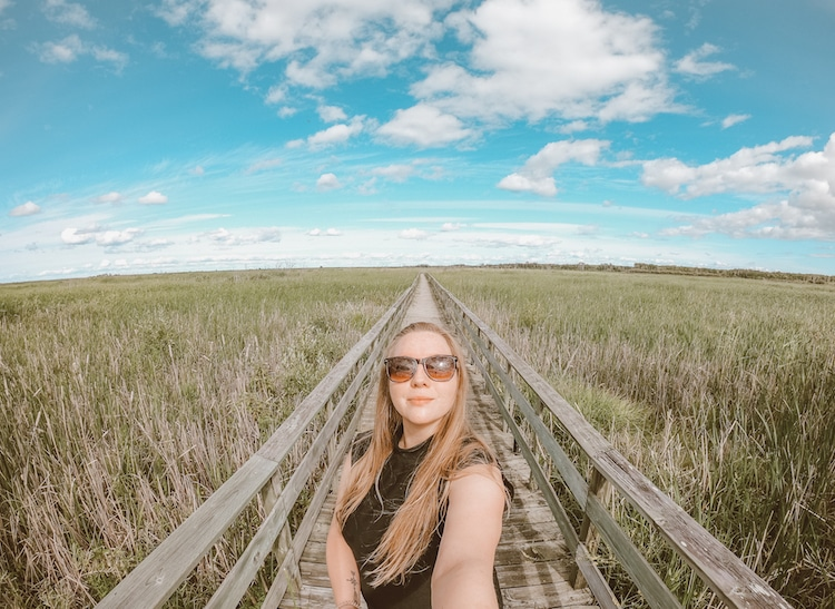Taylor on the boardwalk of the Grassy Narrows Marsh Trail in Hecla Island, Manitoba.