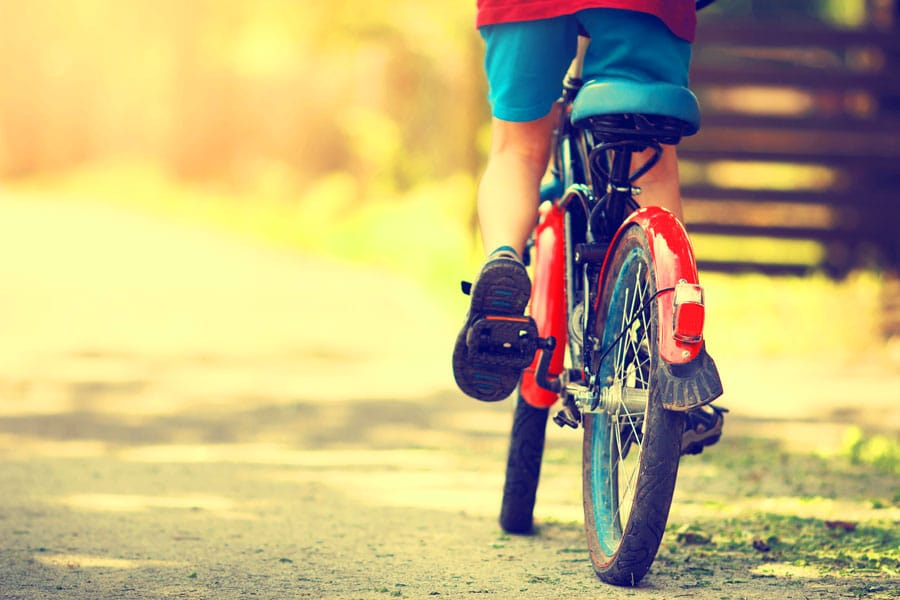 View of a boy riding his bicycle