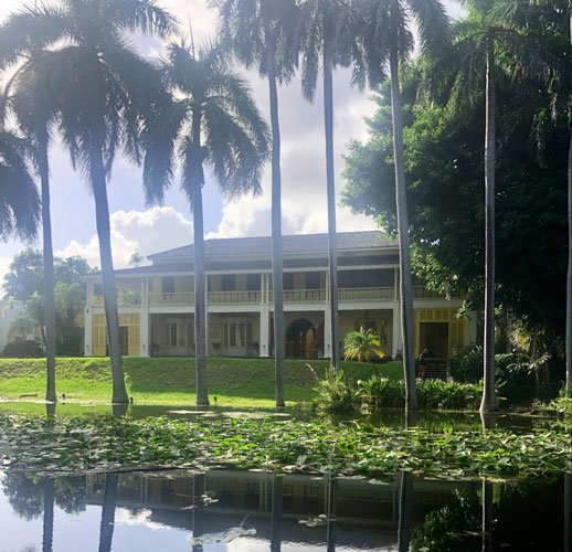 View of the Bonnet House Museum & Gardens from the outside and a pond