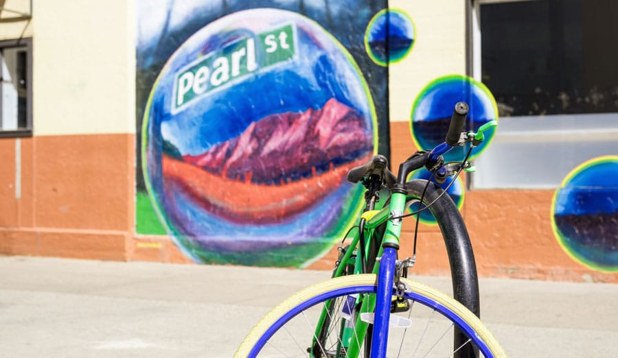 View of a bicycle and a colorful street mural behind it