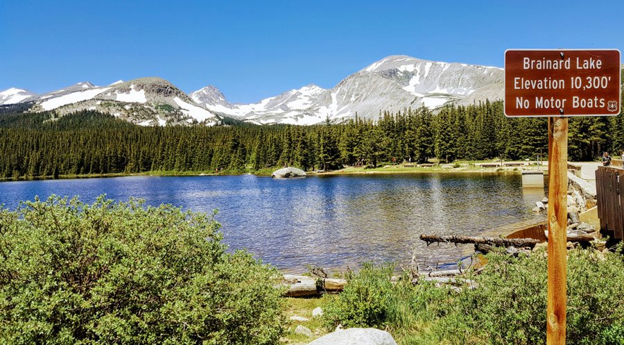 View of the Brainard Lake and a snowy mountain range from the background