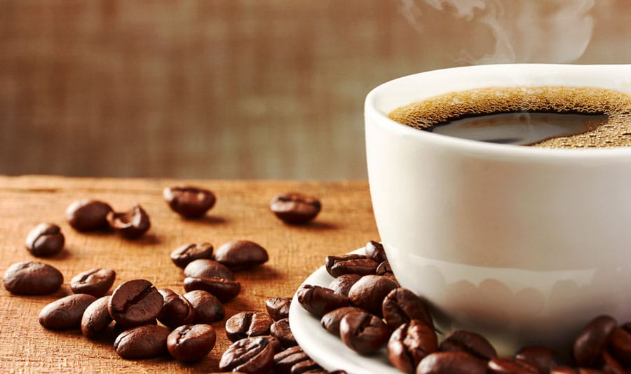 View of a cup of coffee and coffee beans on a table