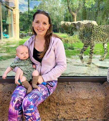 View of the author holding a baby and a cheetah on their background