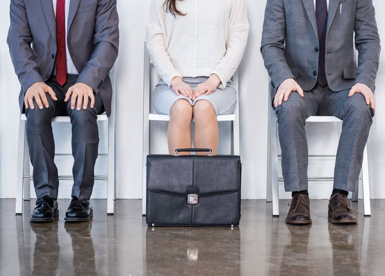 Business people sitting with black case in front.