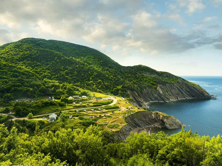 mountain on coastal area with curvy road and few houses on Cabot Trail