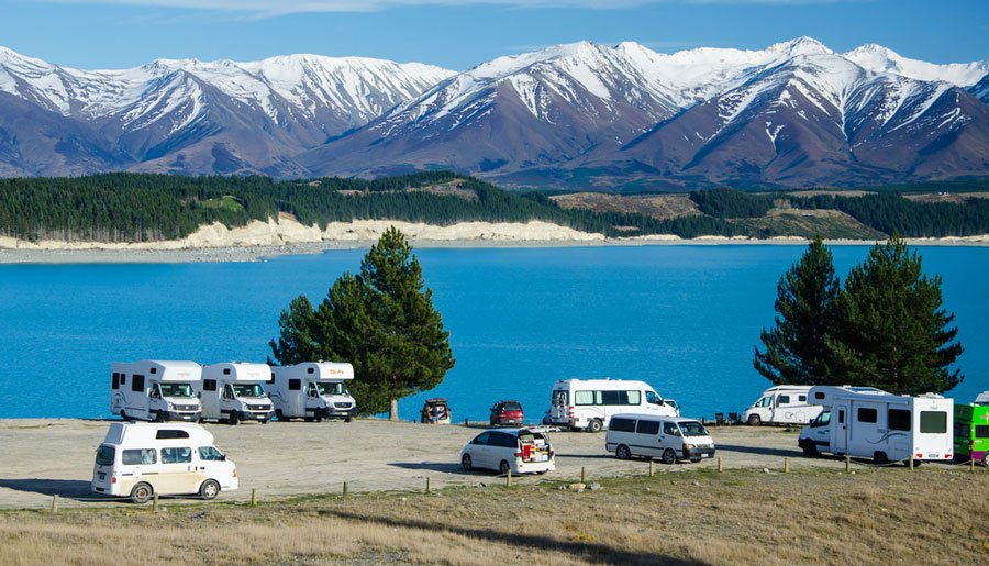 View of campervans with the Lake Pukaki and a snowy mountain on the background