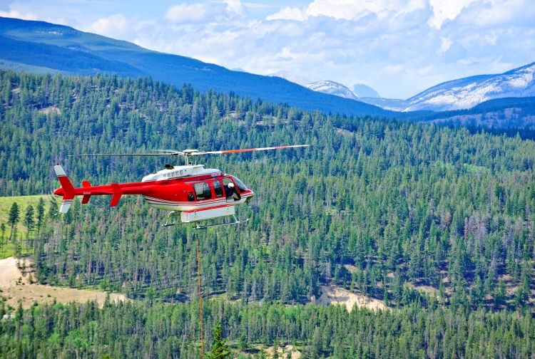 A red emergency helicopter flies over mountains and trees in Canada