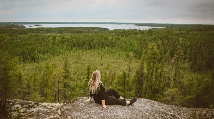 Taylor sits on a large rock in front of Canadian boreal forest and a lake in the distance