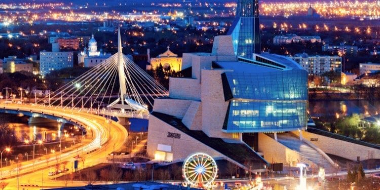 The Canadian Museum of Human Rights at night, with Winnipeg lit up behind it