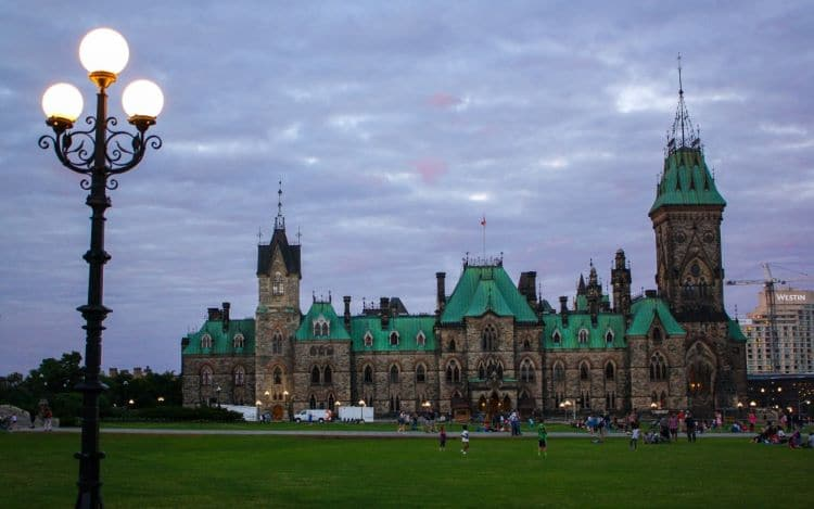 The Canadian parliament building in Ottawa, Canada at dusk, with a lantern in the foreground