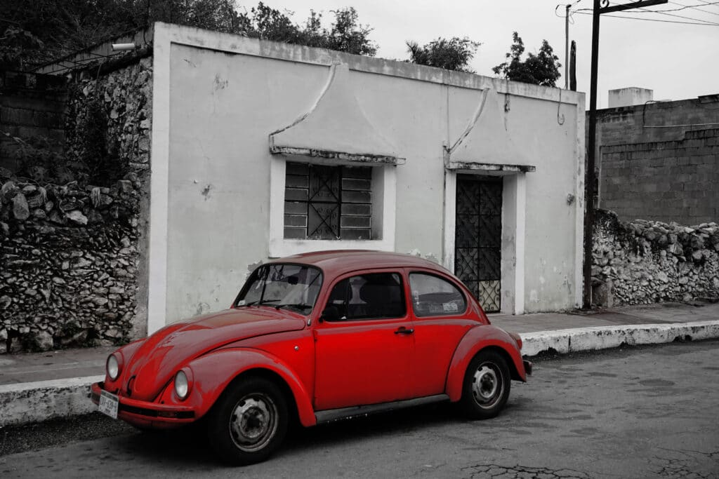 Red car on street in Valladolid Mexico