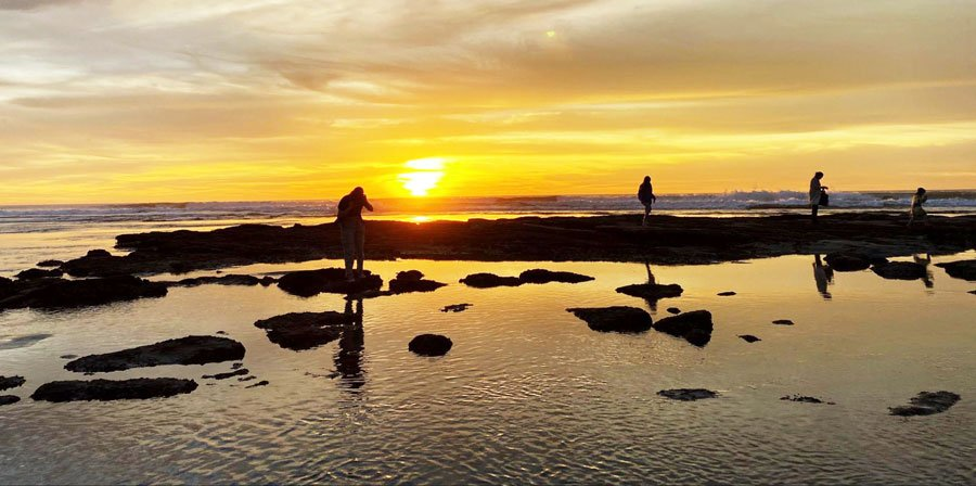 View of a group of people walking on rocks in Cardiff State Beach