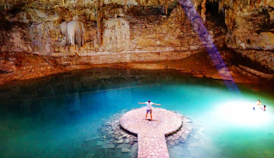 View of a man standing in the middle of Cenote Suytun