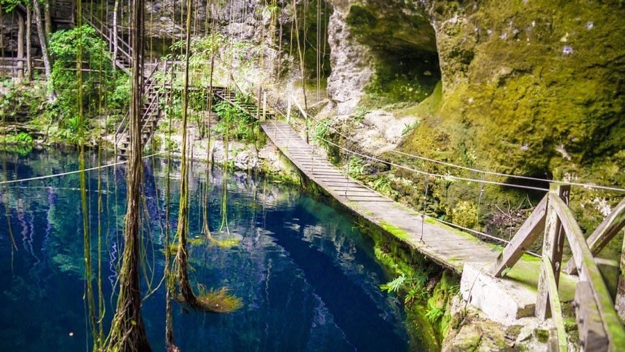 View of a small wooden bridge above the water of Cenote Xcanche