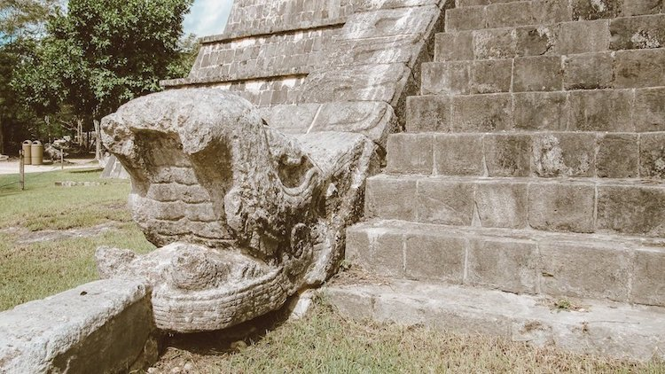 A stone snake head juts out of a pyramid at the site of Chichen Itza in Mexico