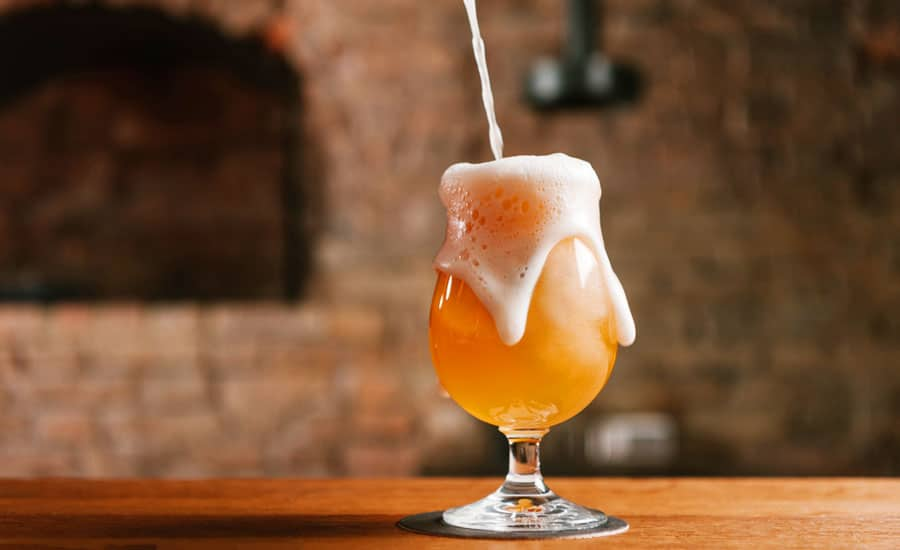 View of pouring a cold beer on a glass