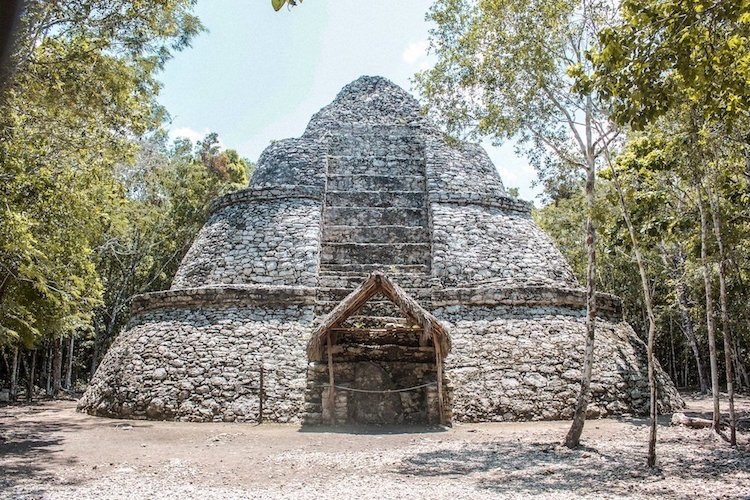 A multi-tiered structure with a straw-roofed door at the Coba Ruins in Mexico