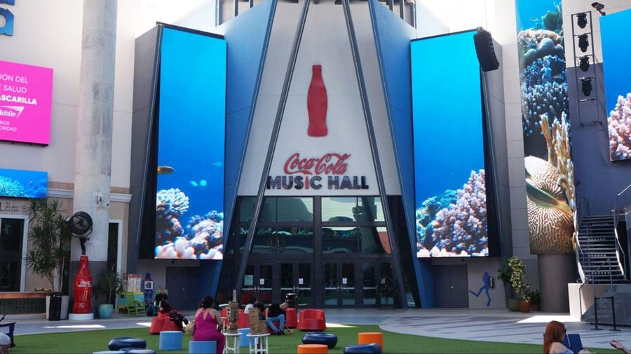 View of the Coca Cola Music Hall entrance and people sitting outside it