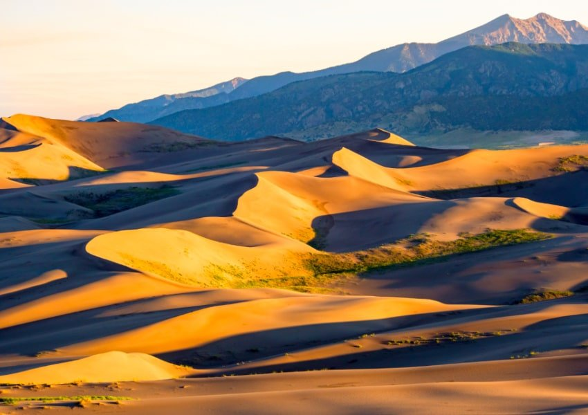 View of sand dunes against mountains at Great Sand Dunes National Park